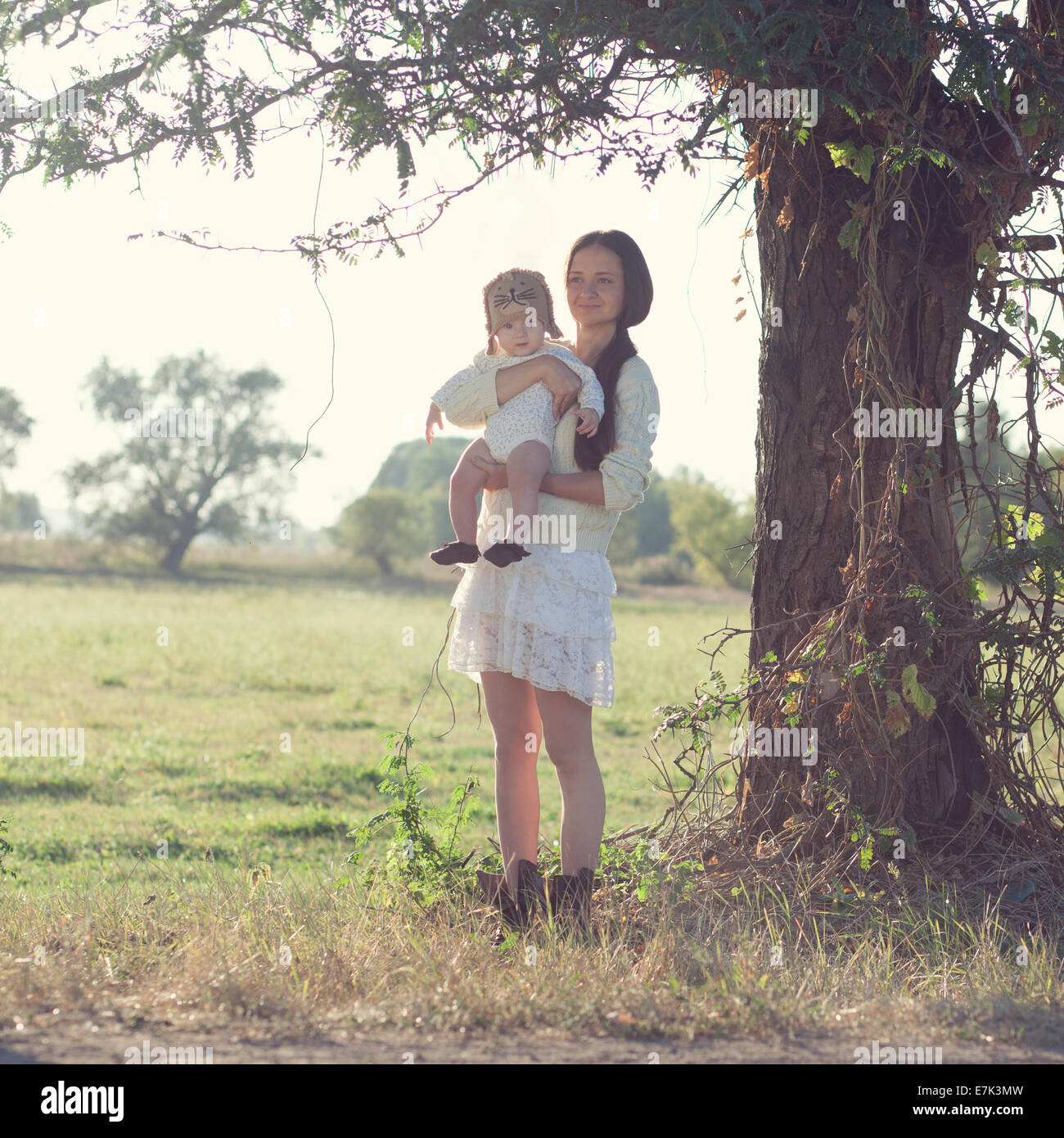 baby and mother strolling on suburban landscape - Stock Image