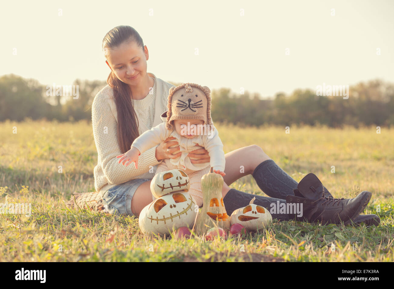 Mother and baby have fun during pumpkin harvest - Stock Image