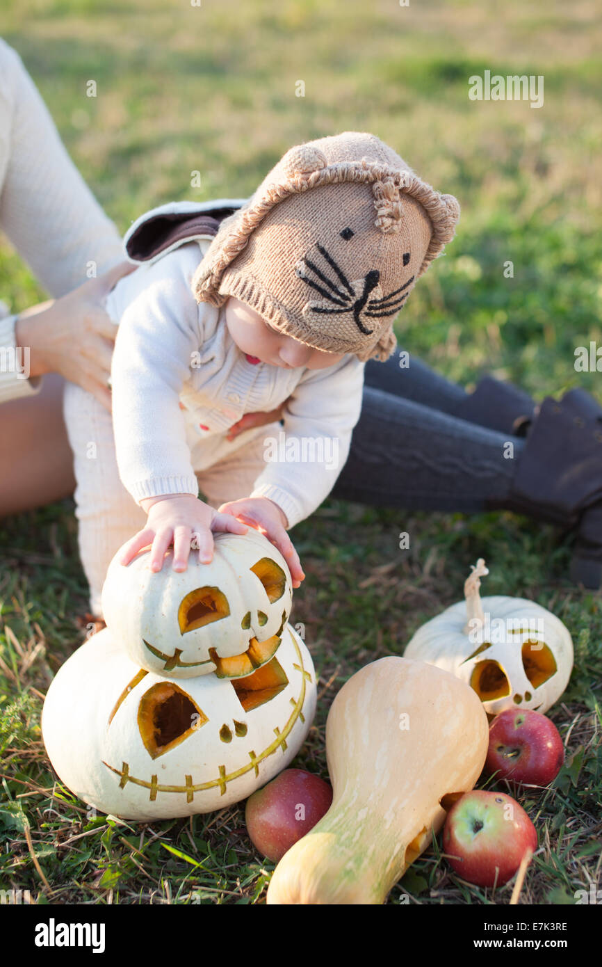 Baby in arms playing with pumpkins - Stock Image