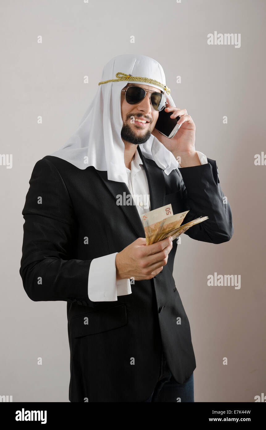The arab man businessman with money, suit and phone cliche - Stock Image