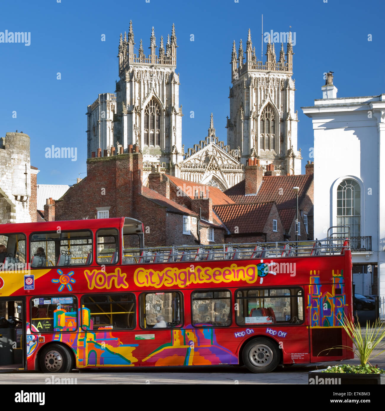 An open topped red double decker bus is parked in St Leonards Square York, with York Minster and Bootham Bar behind, - Stock Image