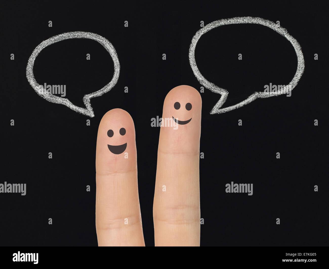Happy fingers with chalk speech bubbles on blackboard, social media concept - Stock Image