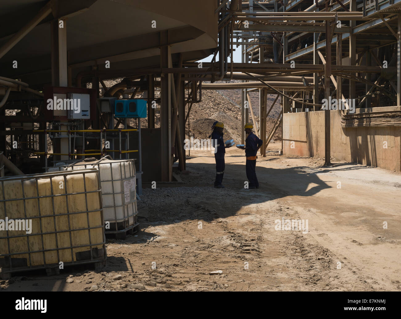 A supervisors converses with a worker in the shade of a beneficiation plant of a large African open pit copper mine. - Stock Image