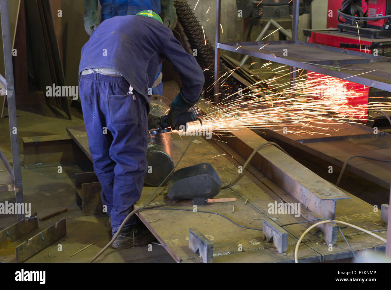 An African artisan boiler maker works with an angle grinder whilst training an apprentice. - Stock Image