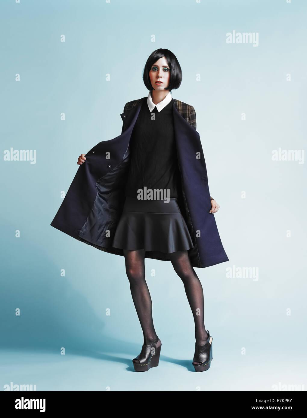 Full length portrait of beautiful young woman wearing an overcoat - studio shot - Stock Image