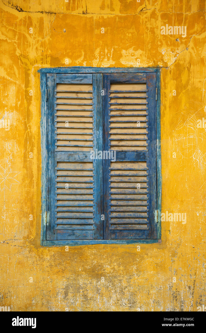 old faded blue and yellow rustic window detail - Stock Image