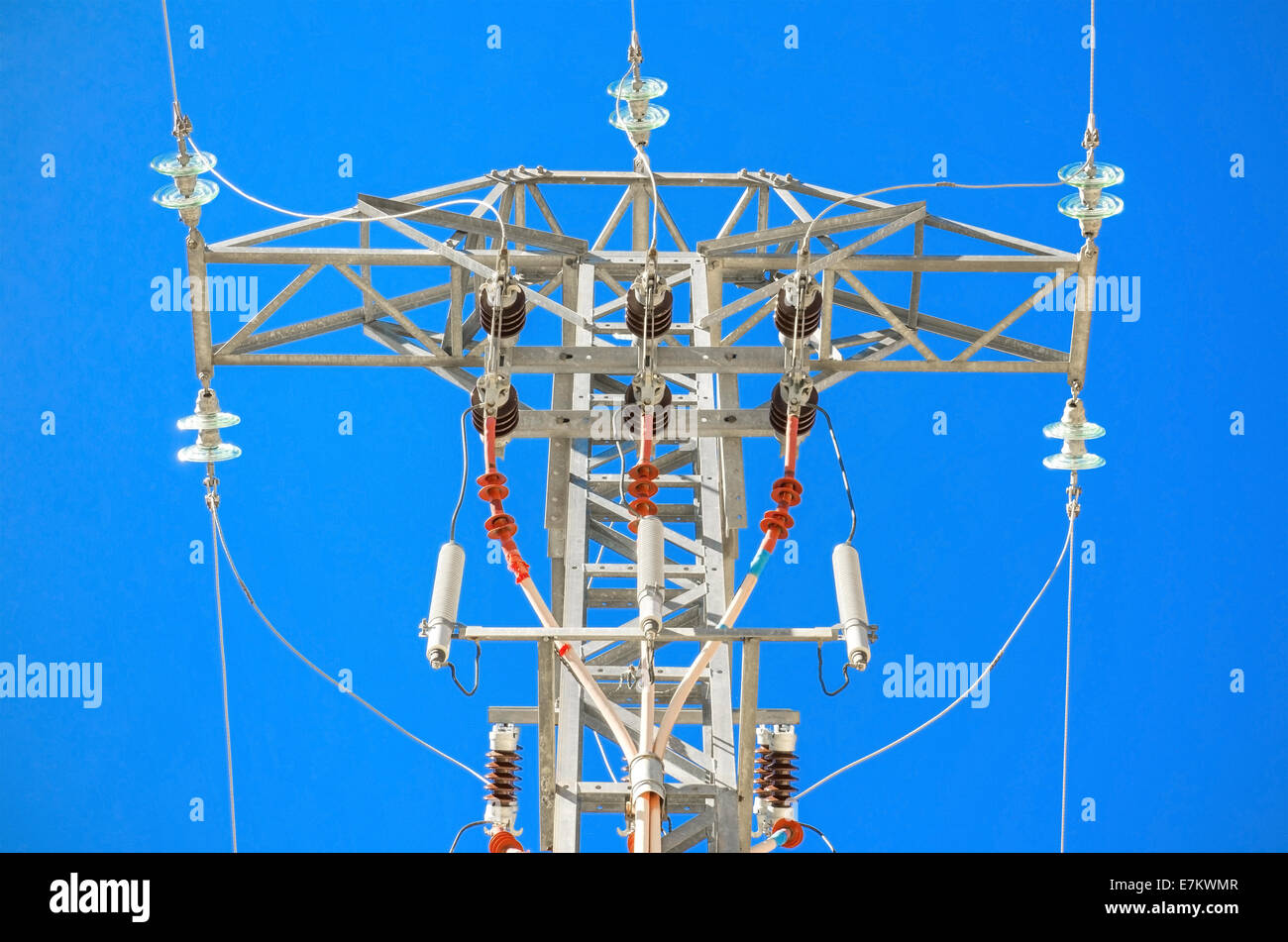 Detailed high voltage power line over brightly blue sky. - Stock Image