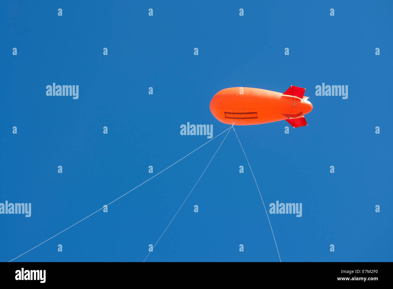 Orange blimp against a blue sky, Cambridgeshire - Stock Image