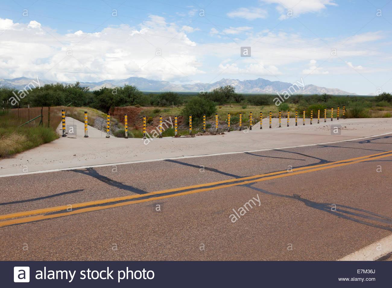 Steel pipe barricade where desert wash crosses highway Arizona - Stock Image