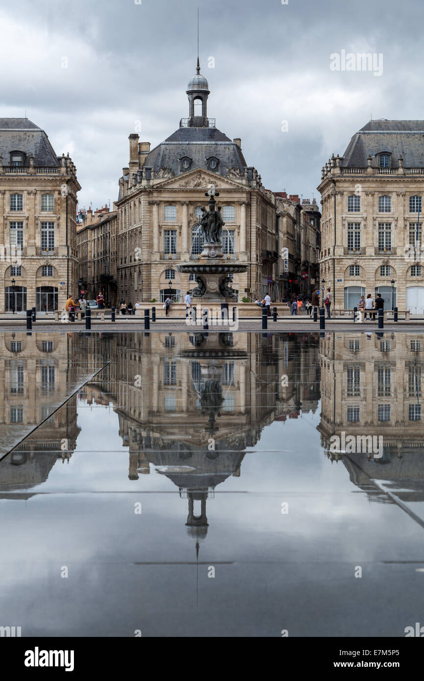 The historic architecture is reflected in the black granite of the Water Mirror in Bordeaux France - Stock Image