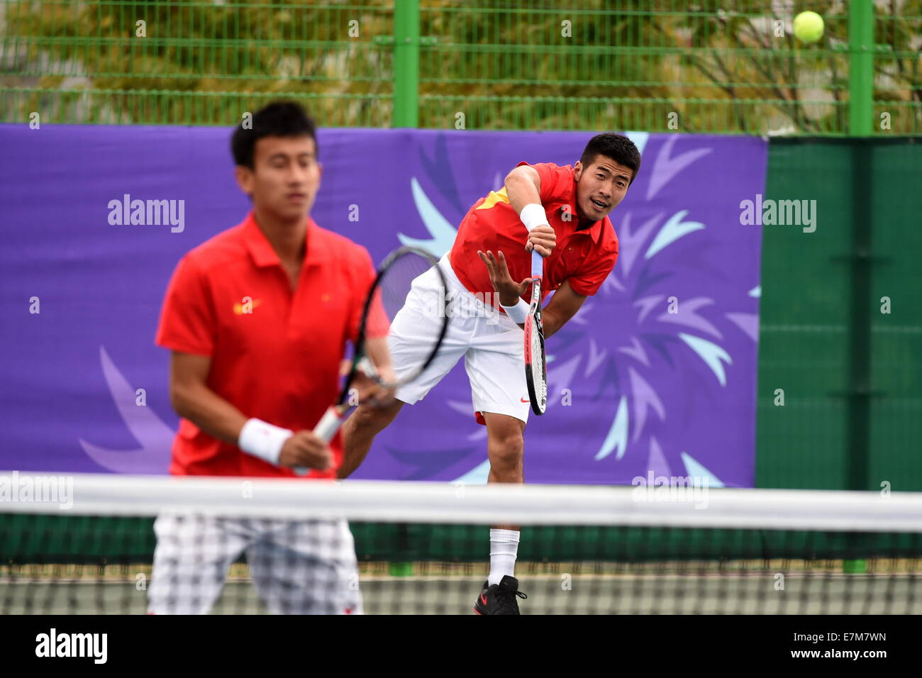 Incheon, South Korea. 21st Sep, 2014. Li Zhe (back) of China serves the ball during the men's tennis team second - Stock Image