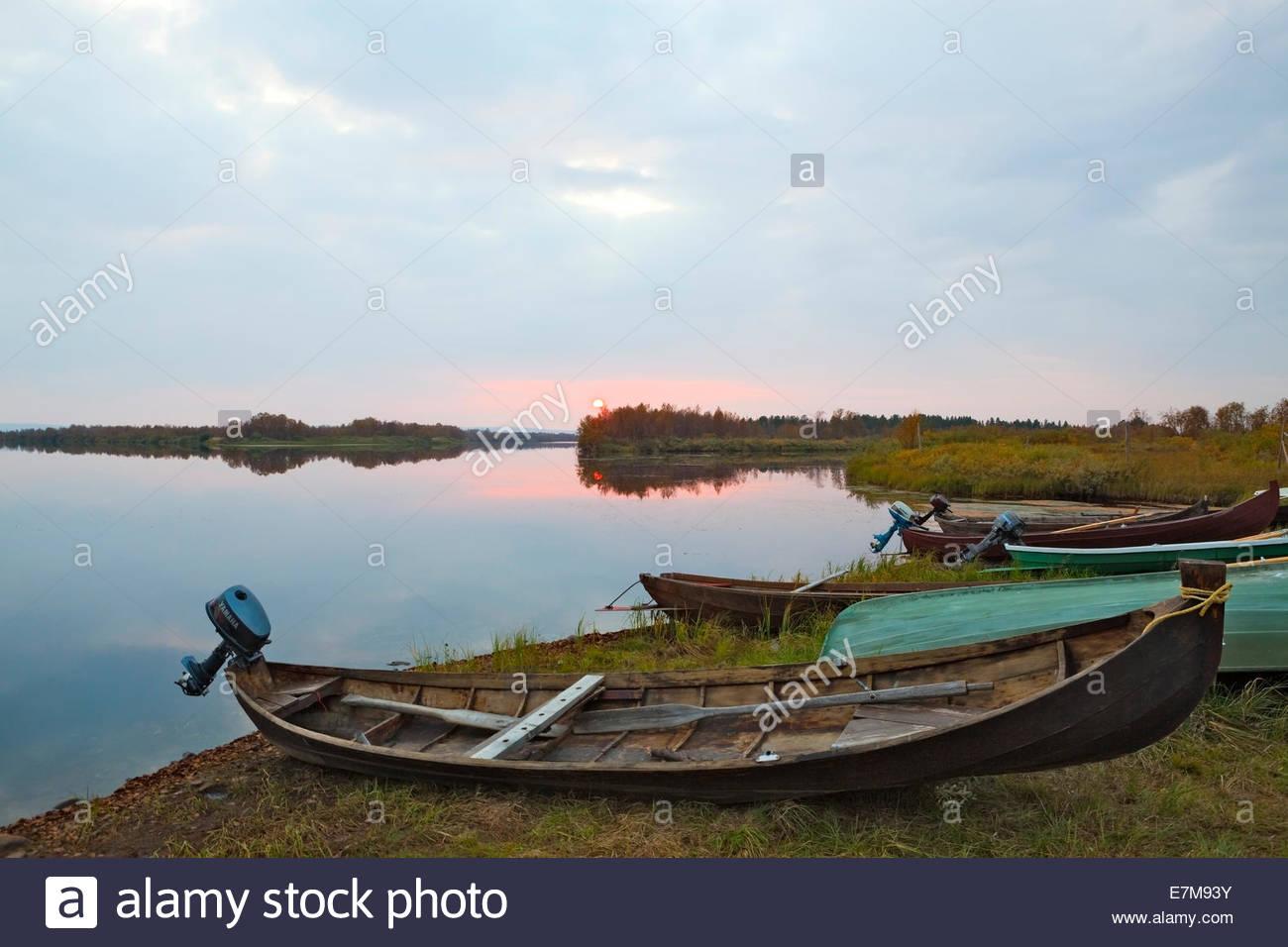 Boats on shore of Muonio River - Stock Image