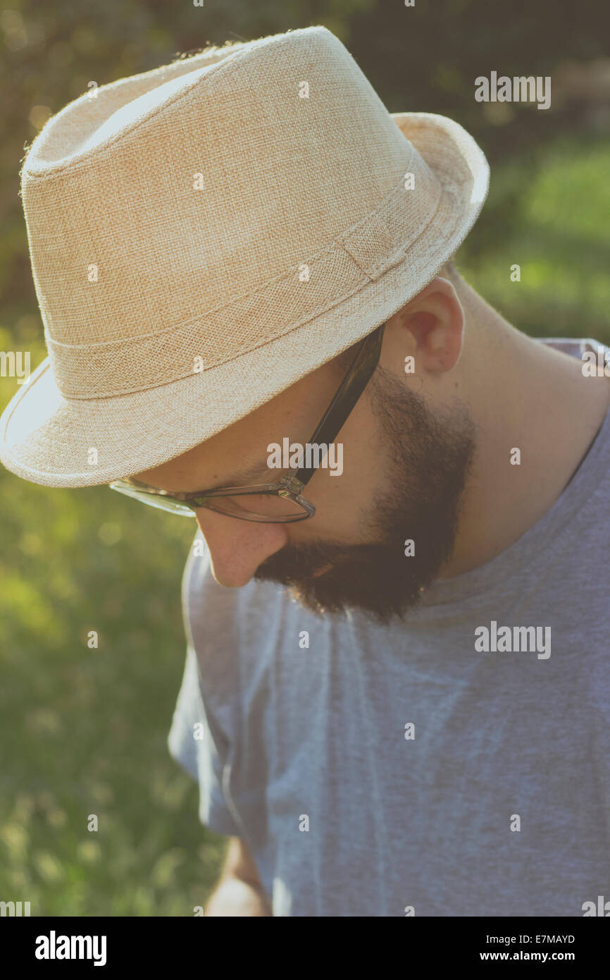 Portrait of a bearded young hipster man daydreaming, looking away. Retro tones - Stock Image