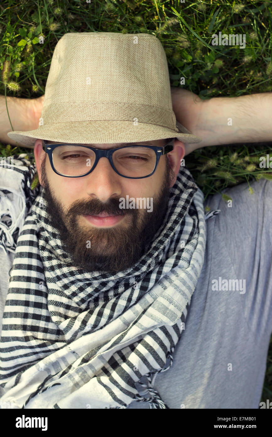Portrait of a bearded smiling young hipster man lying in the grass and daydreaming - Stock Image