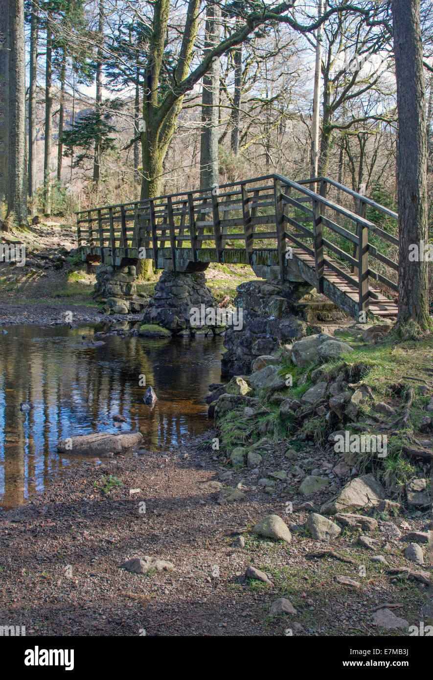 A wooden bridge over a tributary of the River Esk near Boot in the Lake District Cumbria England - Stock Image