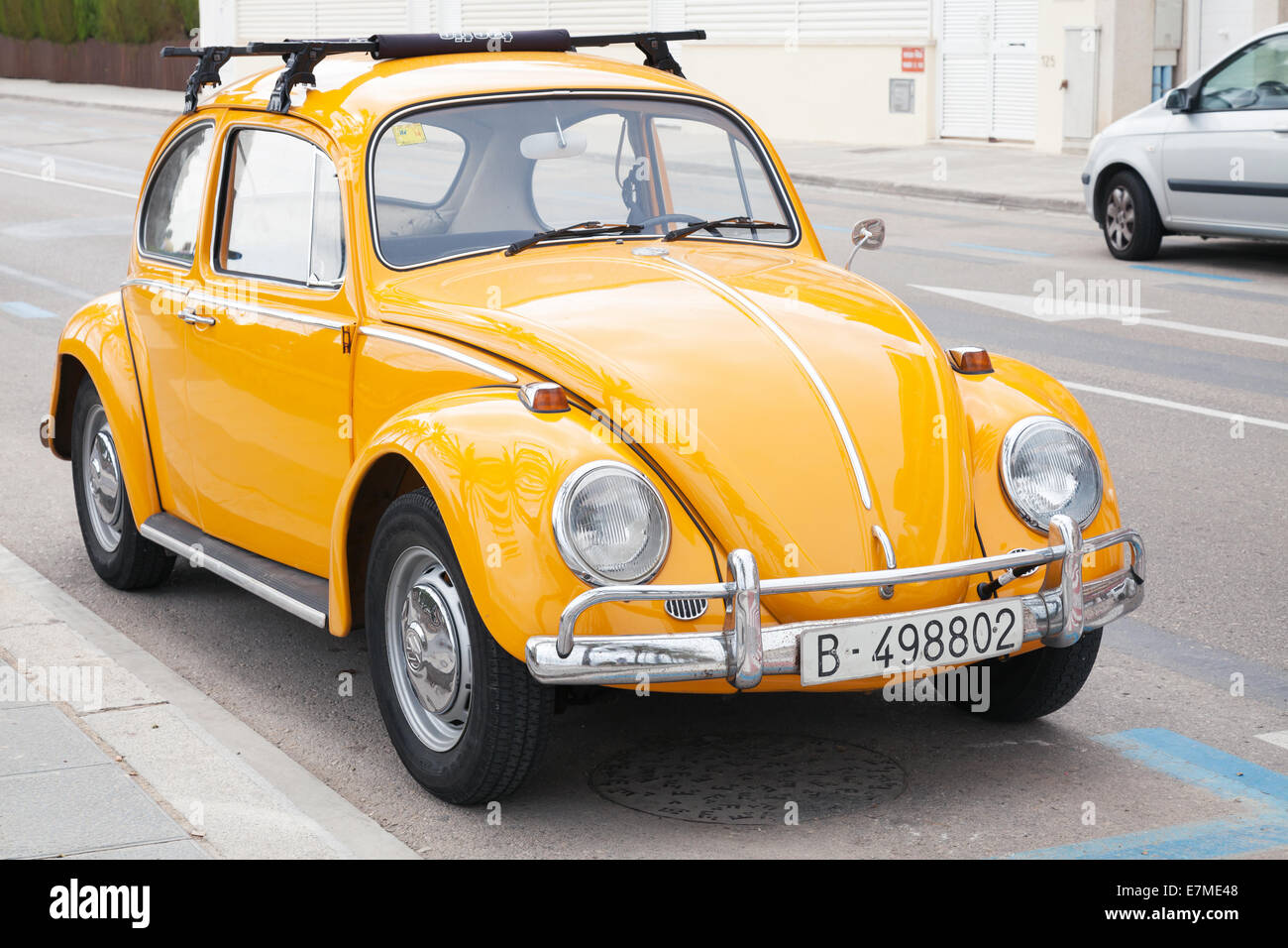 Yellow Volkswagen Kafer stands parked on the roadside - Stock Image