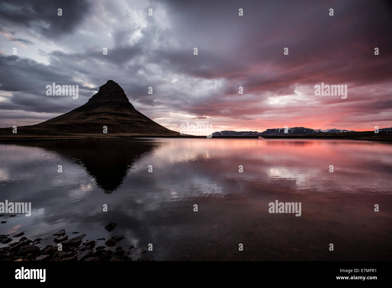 The Kirkjufell mountain reflected in the water of Grundarfjordur bay at sunrise, Snaefellsnes Peninsula, in western - Stock Image