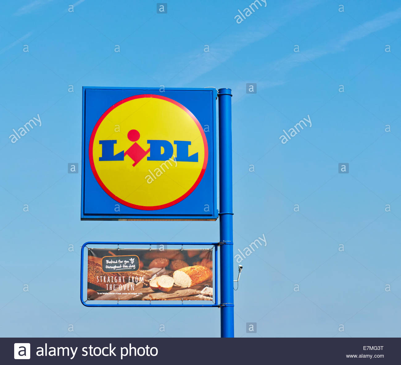 blue yellow logo sign of lidl supermarket against blue sky - Stock Image