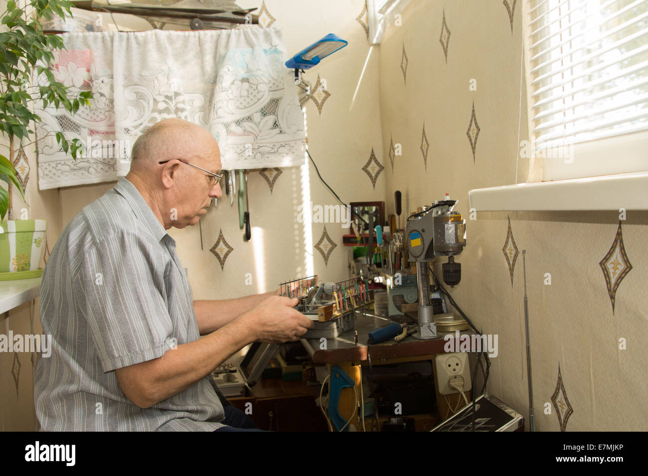 Retired Man Working At Home On His Handicrafts Sitting At A Compact