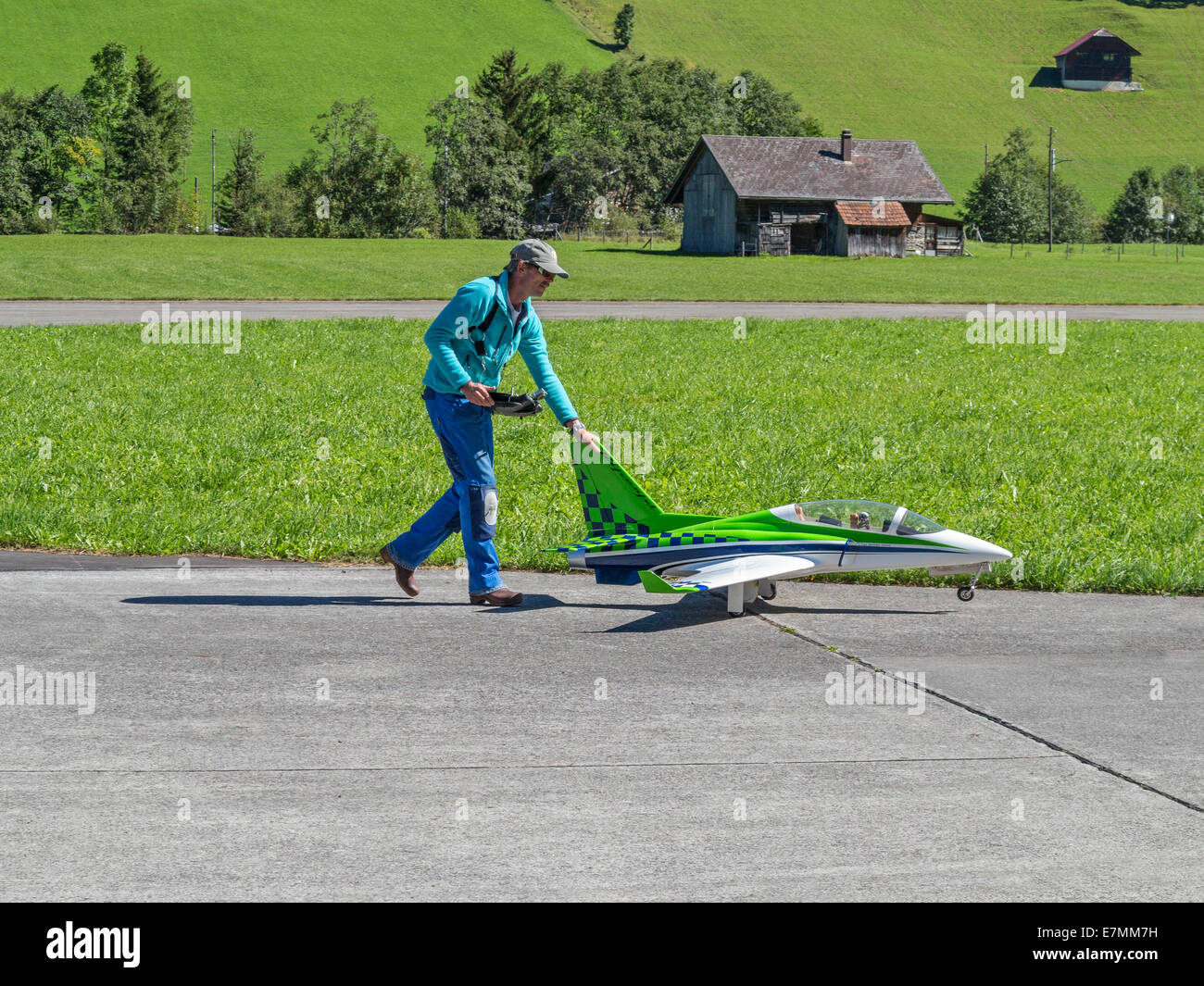 Model aircraft enthusiast wheeling his jet aircraft out ready to fly - Stock Image