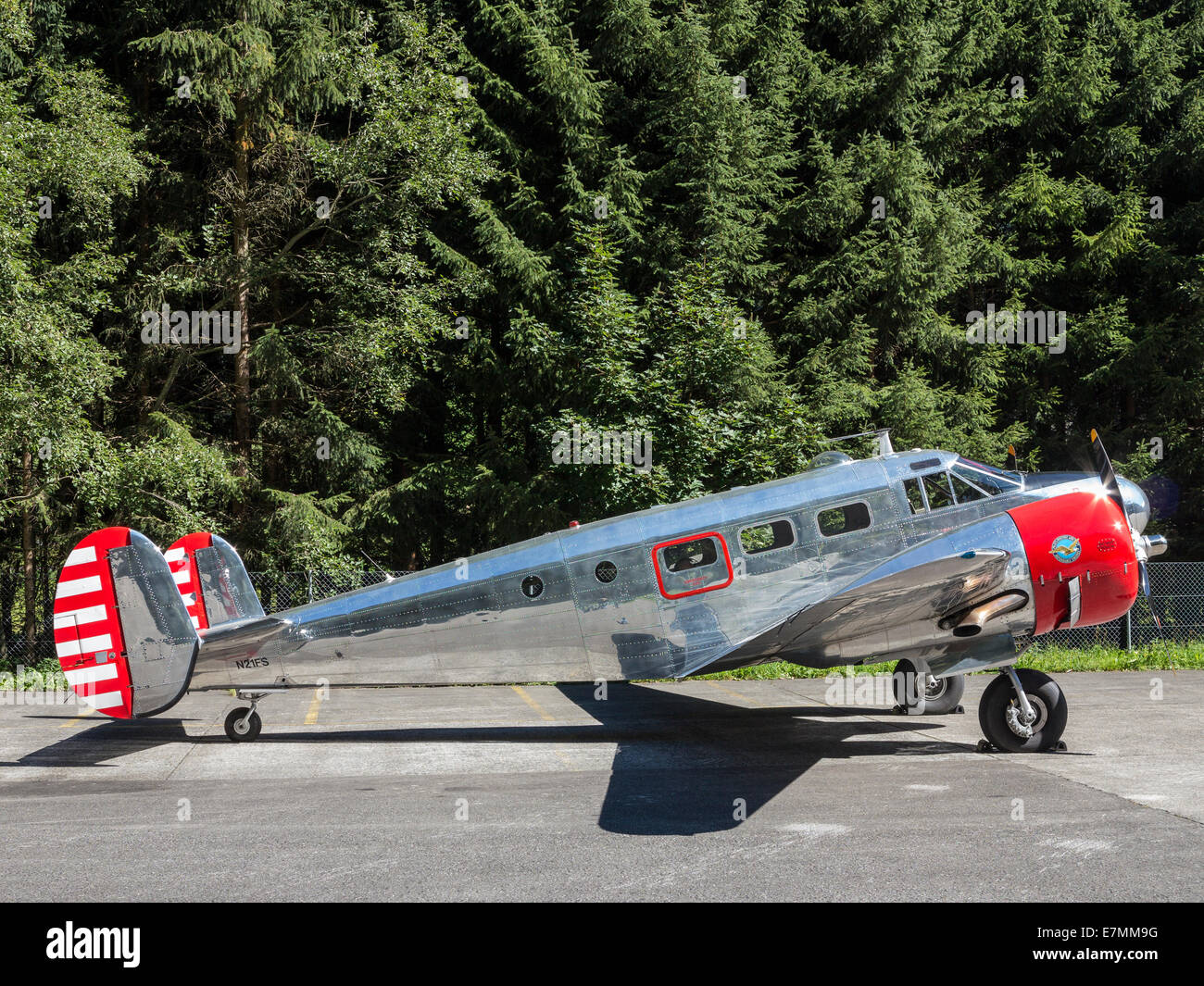 A veteran Beechcraft Twin aircraft (Beechcraft Model-18) parked against a background of trees. - Stock Image