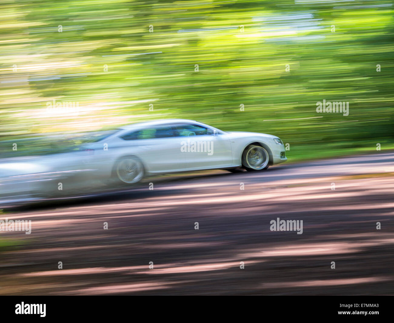 Acceleration. Foot down hard on a woodland road. Panning, motion blur and camera angle used to give the effect - Stock Image