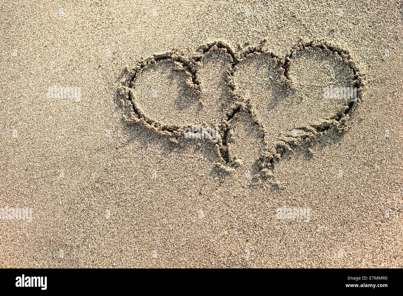 Two hearts written on the sand. - Stock Image