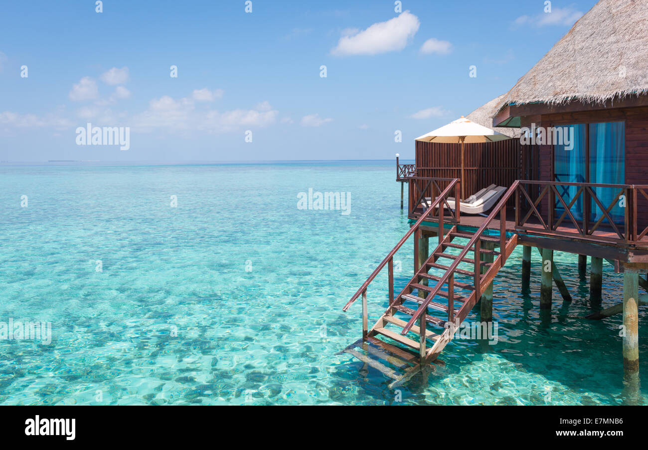 Turquoise lagoon in a tropical ocean, part of over-water bungalow with steps into the water. - Stock Image