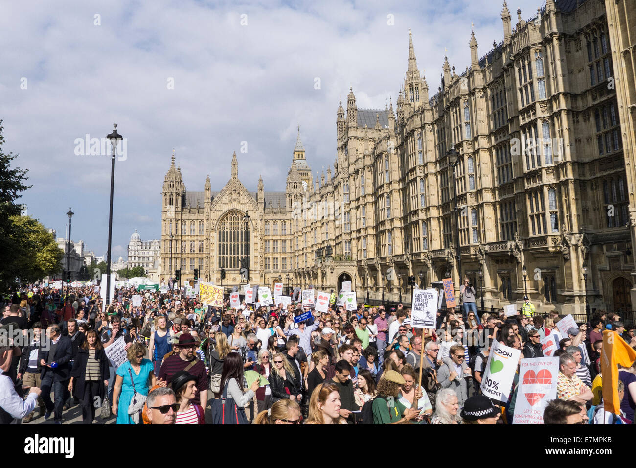 A mass of protesters with placards march in front of the Houses of Parliament during the Climate Change demonstration, - Stock Image