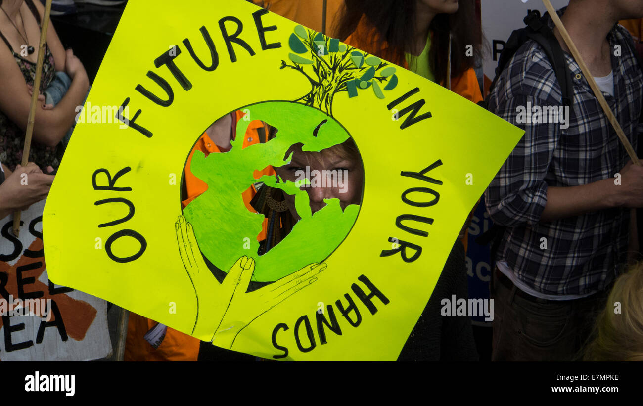 A demonstrator peers through her placard which says 'Our Future In Your Hands' during the Climate Change - Stock Image