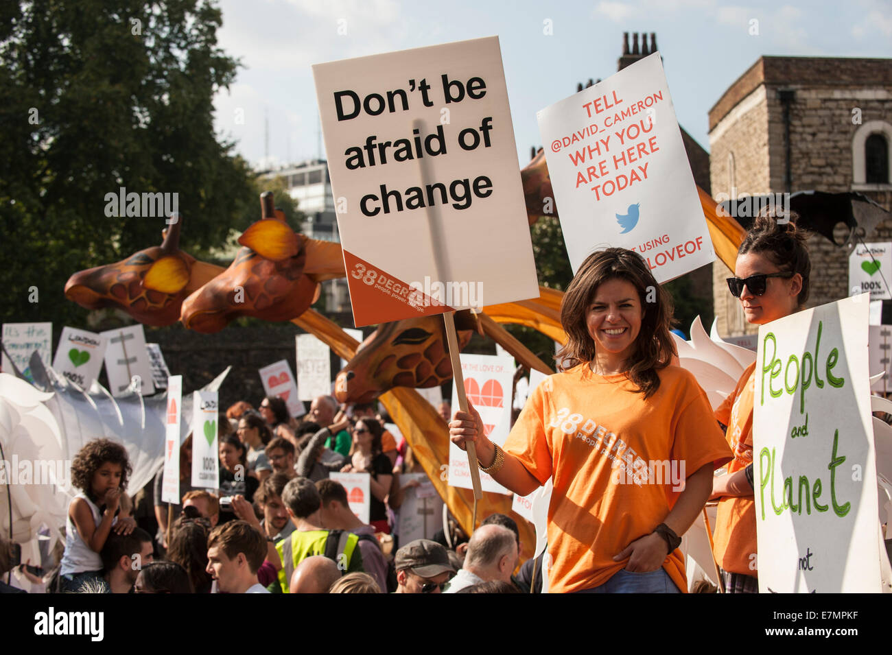 A demonstrator holds a placard which says 'Don't Be Afraid Of Change' as she marches in front of the - Stock Image