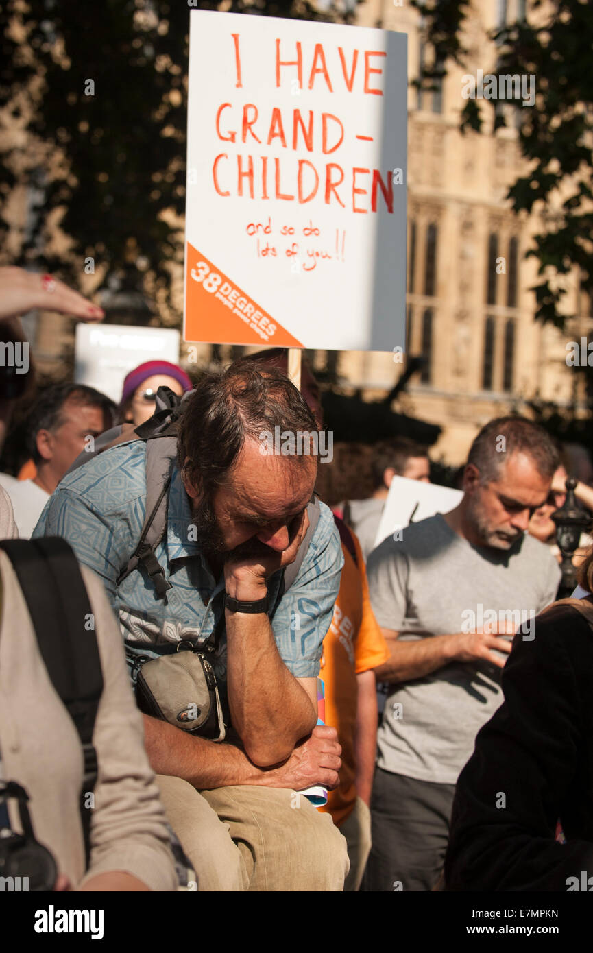 A demonstrator sits dejectedly under a placard which says 'I Have Grandchildren and so do lots of you!!' - Stock Image
