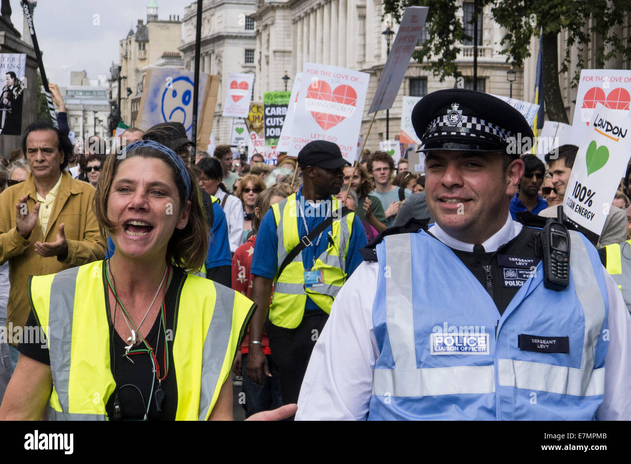 A steward walks next to a police liaison officer at the front of the Climate Change demonstration, London, 21st - Stock Image