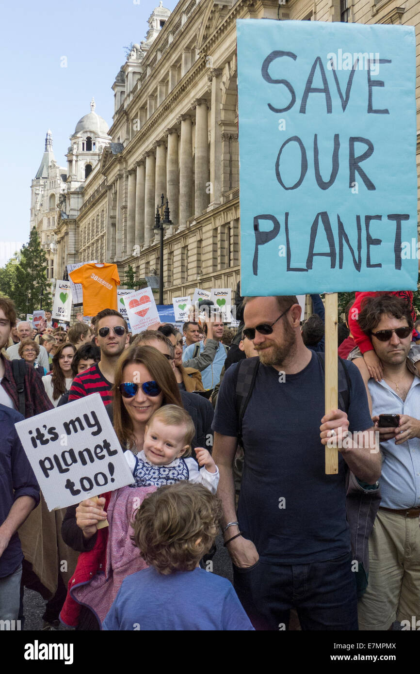 A family marches holding placards; the father's says 'Save Our Planet', the baby has 'it's my - Stock Image