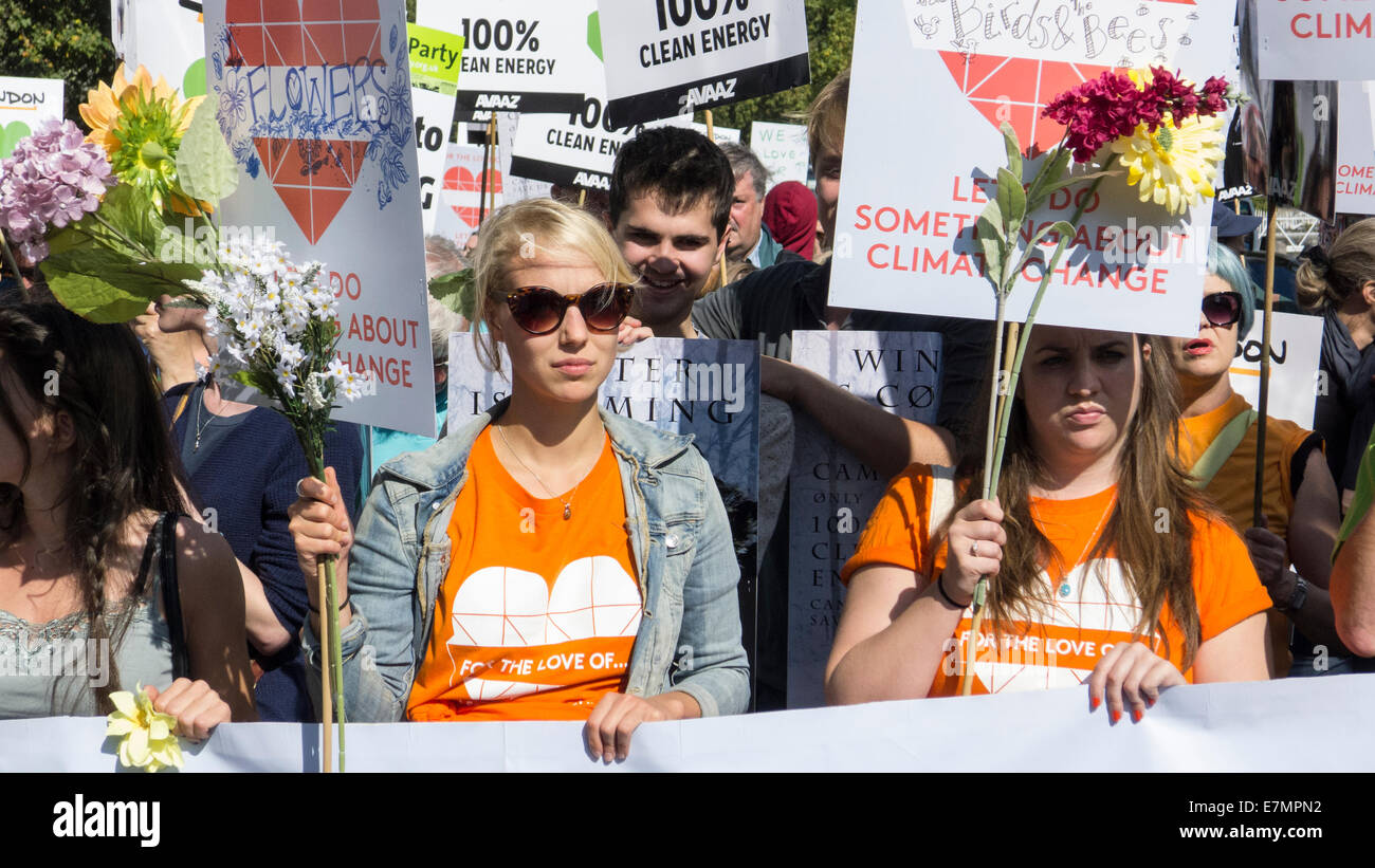 Protesters hold placards saying 'let's do something about climate change' decorated with flowers at - Stock Image