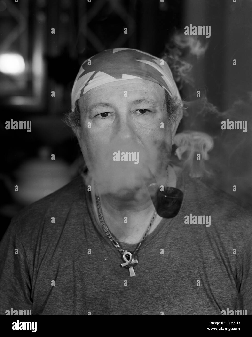 Bill Goldman is smoking his pipe and it smoke is all over him. - Stock Image