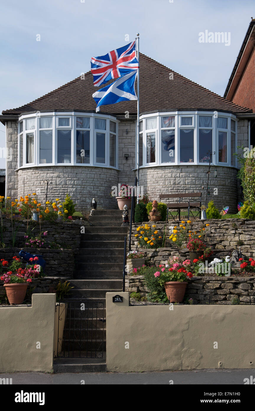 United Kingdom flags. The Union Jack and Scottish Saltire fly above a bungalow in England during the 2014 Scottish independence referendum campaign. Stock Photo
