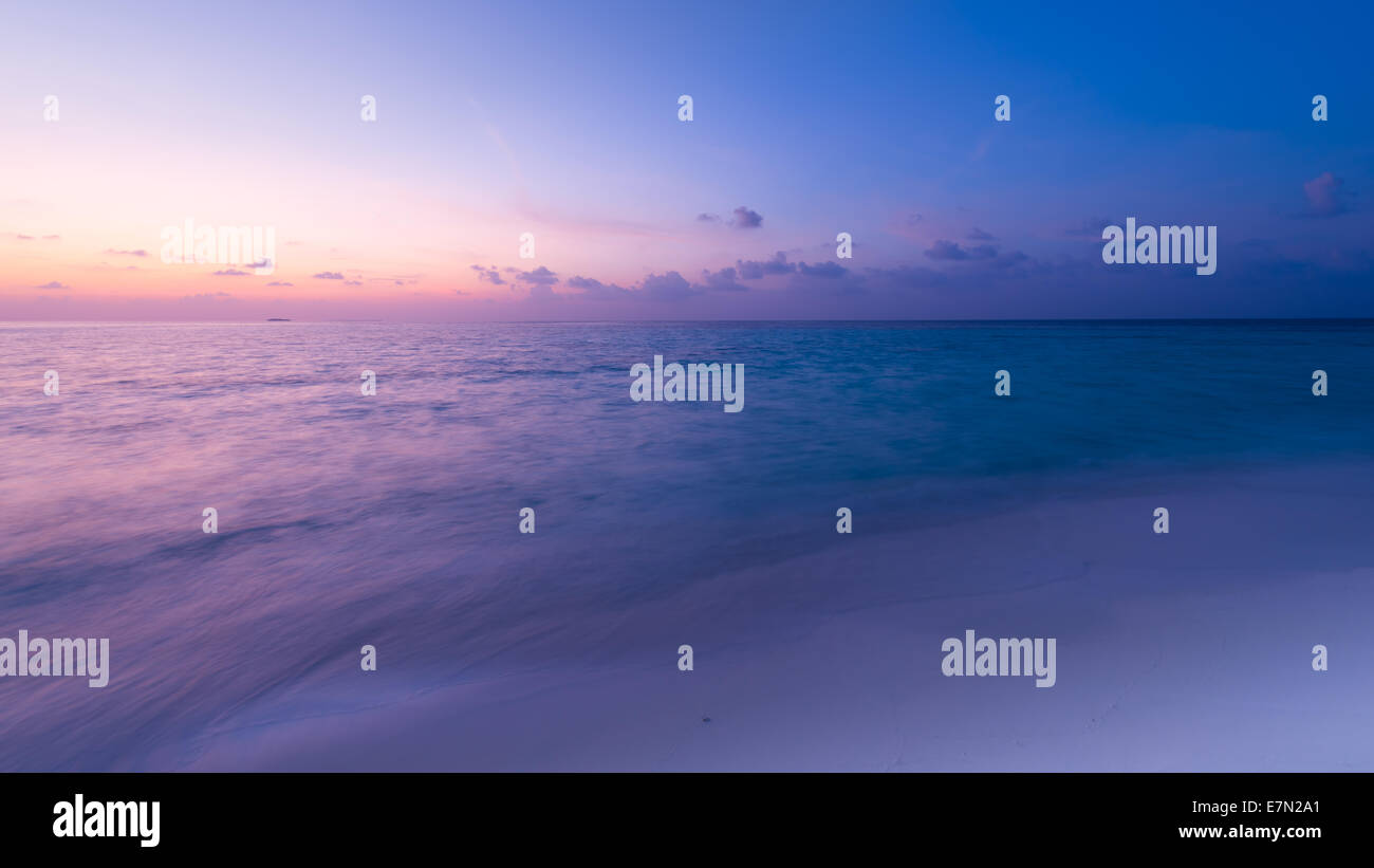 Gorgeous sunset over the ocean. Splash of waves on the white sand beach. Panorama of tropical island. Maldives - Stock Image