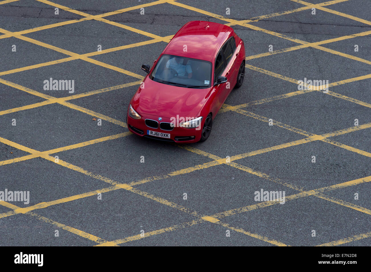 A red car in a yellow box junction. - Stock Image