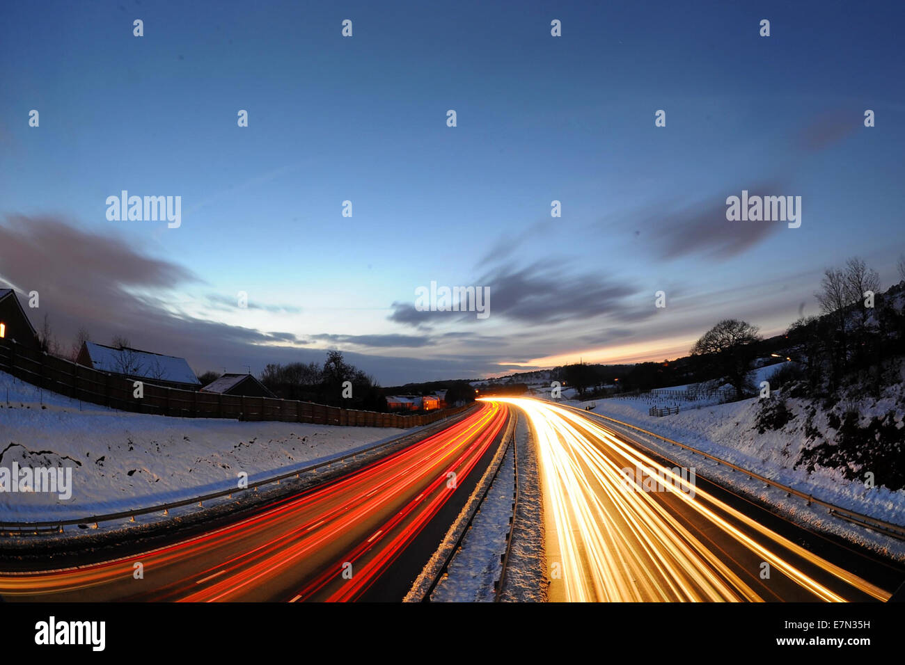 Heavy motorway traffic at rush hour at night on the M4 in the UK following snow fall. - Stock Image