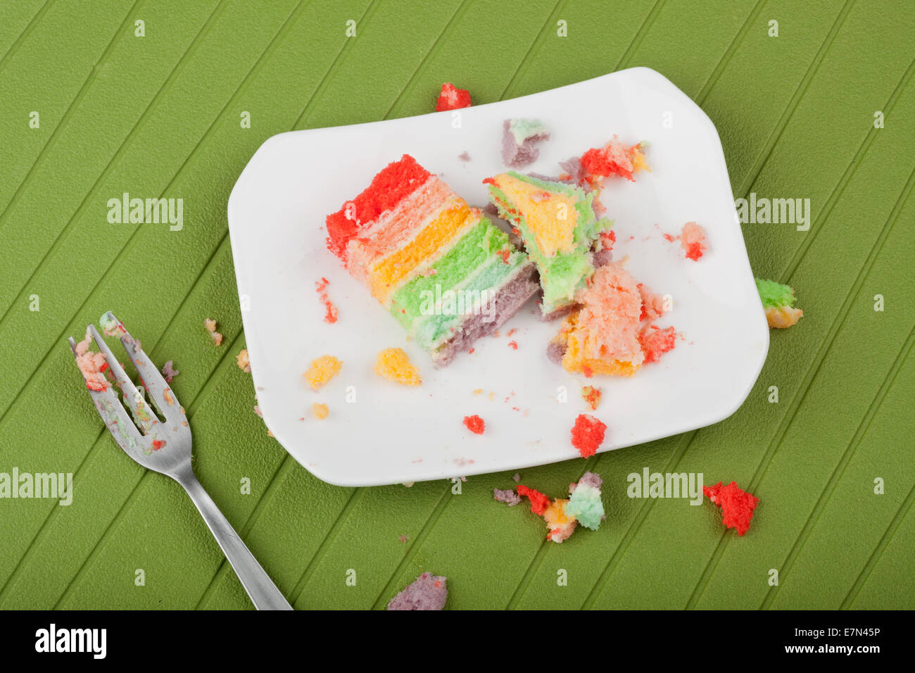 Messy leftover rainbow cake on a plate with crumbs around it - Stock Image