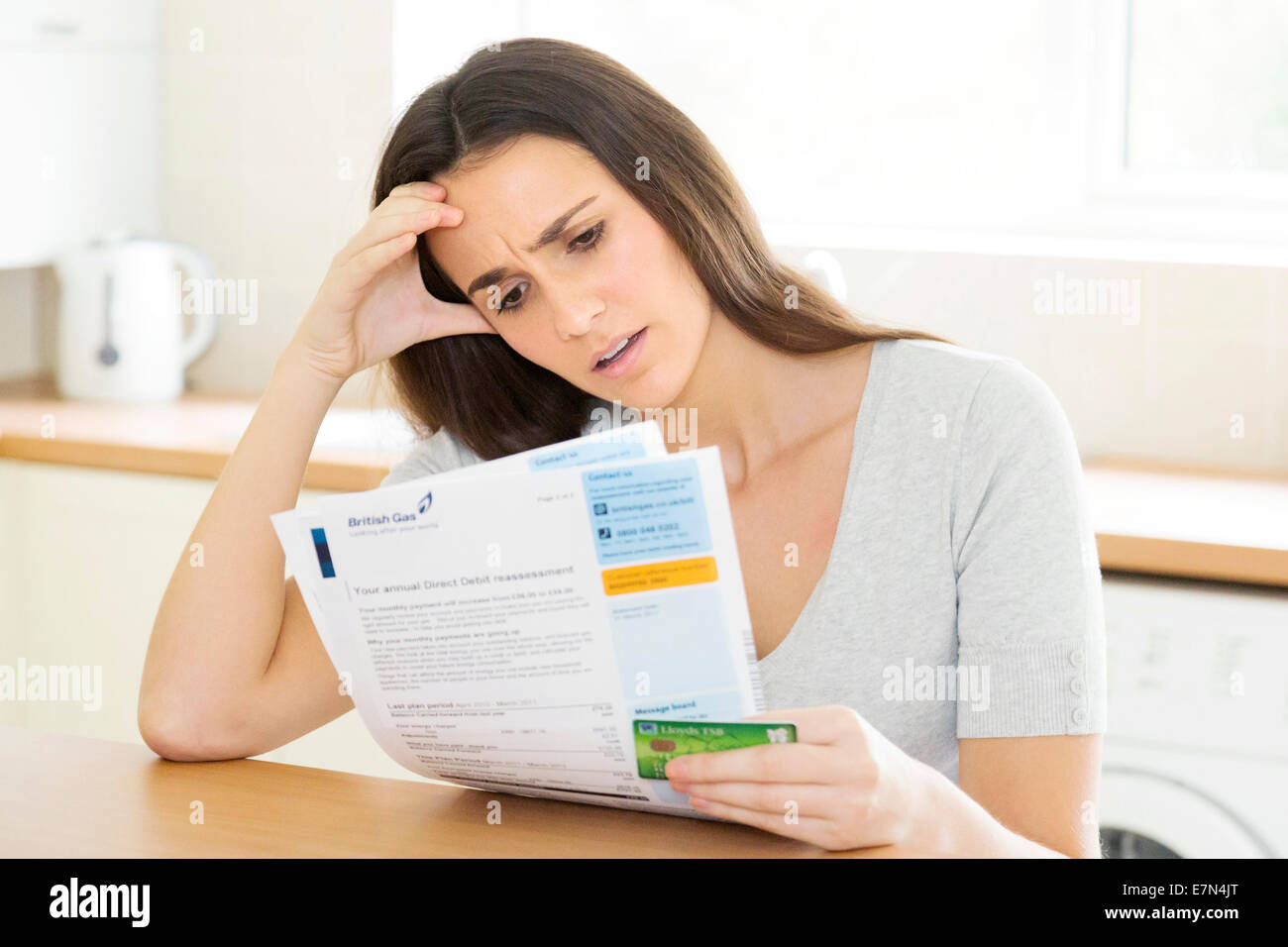 woman worried about her gas utility bill / statement - Stock Image