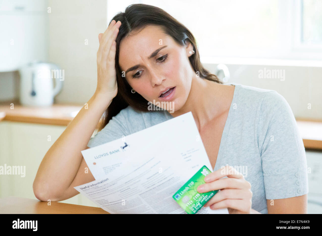 woman worried about bank / credit card statement - Stock Image