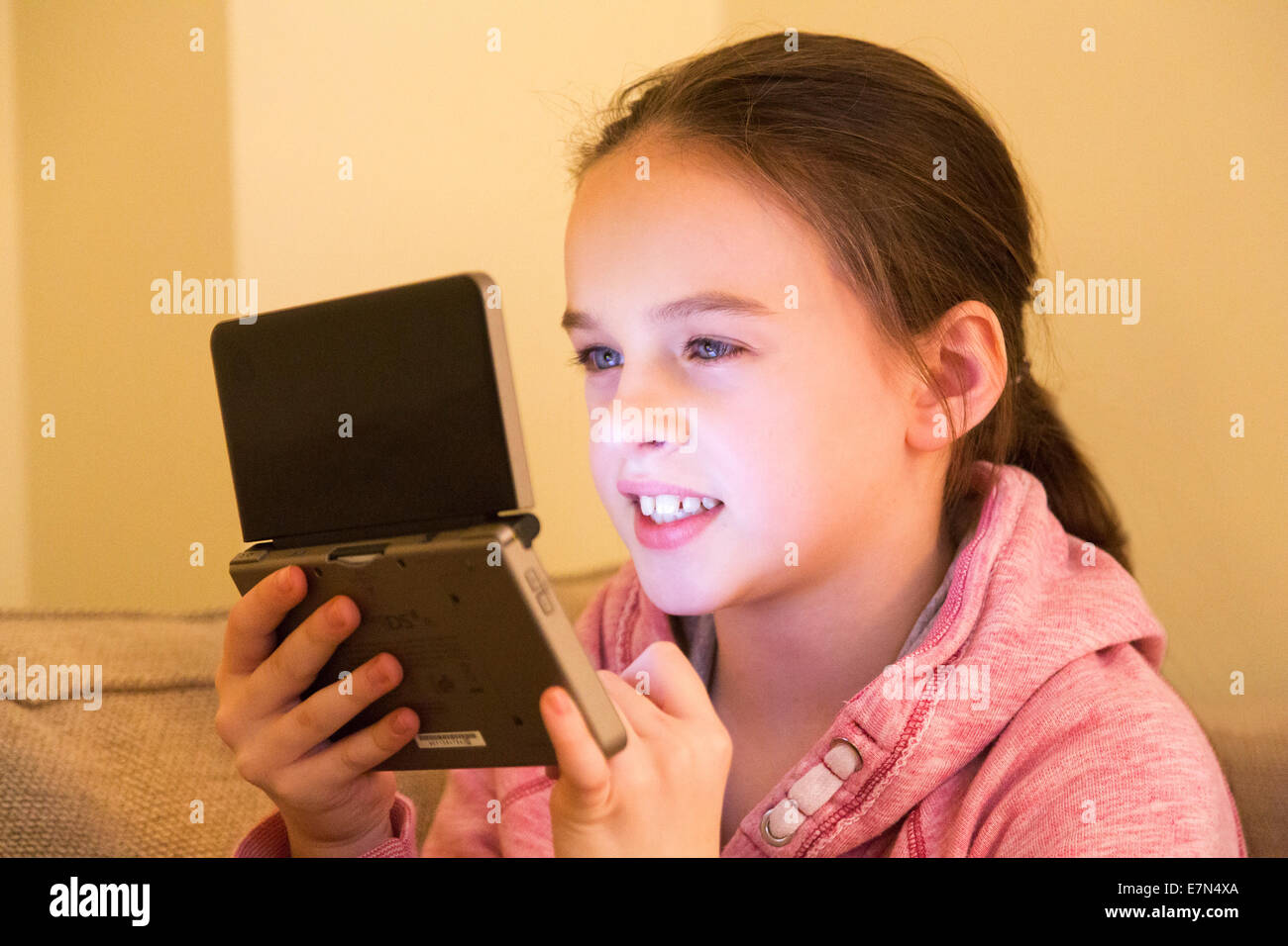 young girl using Nintendo DS games console - Stock Image