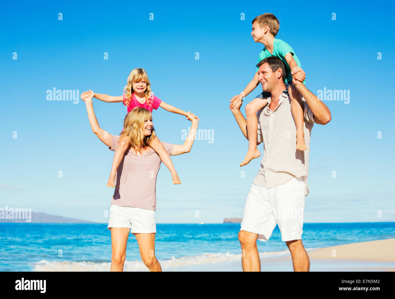 Happy Healthy Family of Four having Fun on Tropical Beach - Stock Image