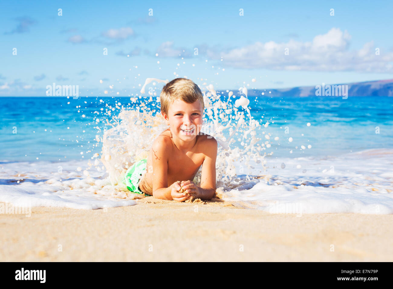 Happy Young Boy on the Beach Lying in the Sand Playing in the Waves - Stock Image
