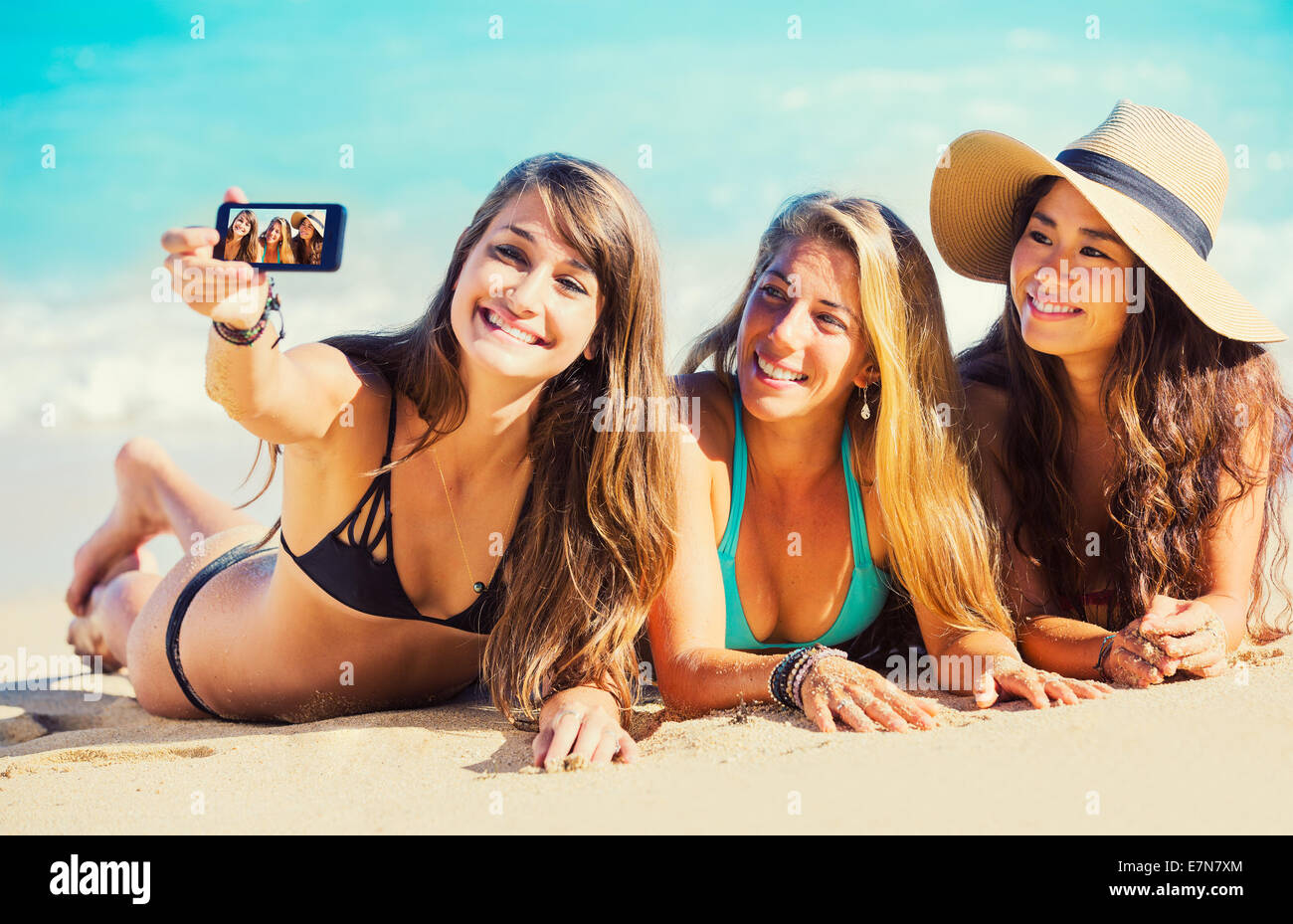 Girls having fun at the beach taking self portrait with smart phone. Summer Fun Lifestyle. - Stock Image