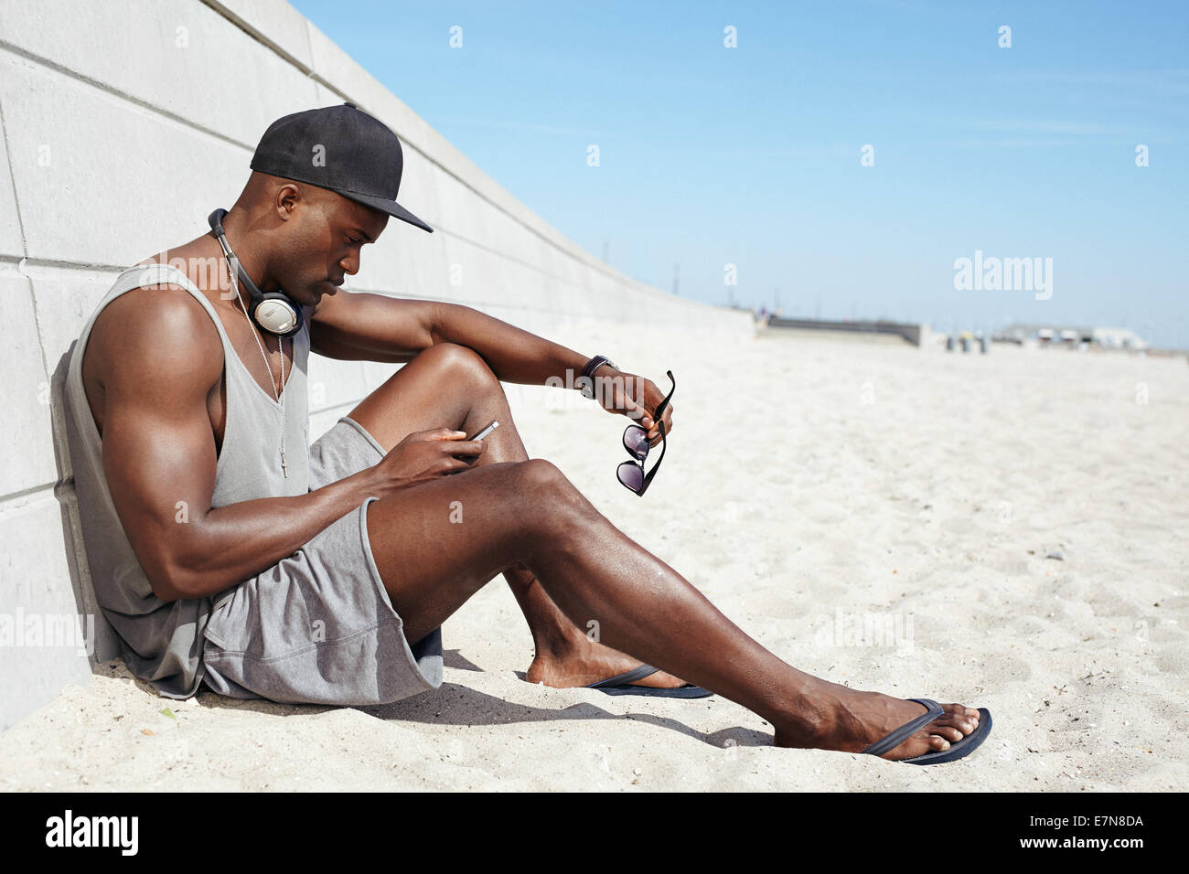 Young guy sending a text message at the beach. African man sitting on beach using mobile phone. Muscular male model Stock Photo