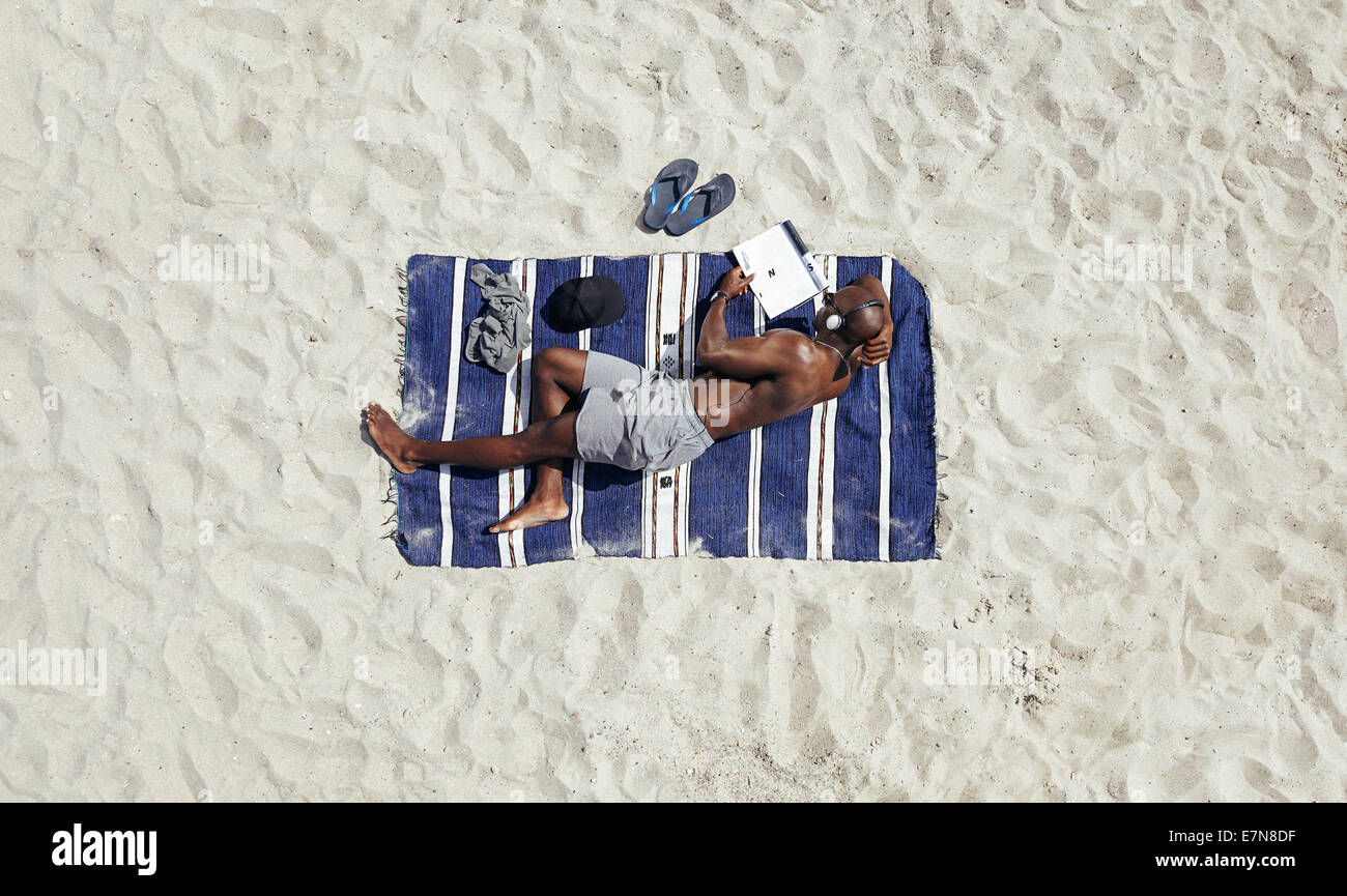 Shirtless young African man lying on a mat reading a book on a sunny day. Young guy relaxing on beach reading and - Stock Image