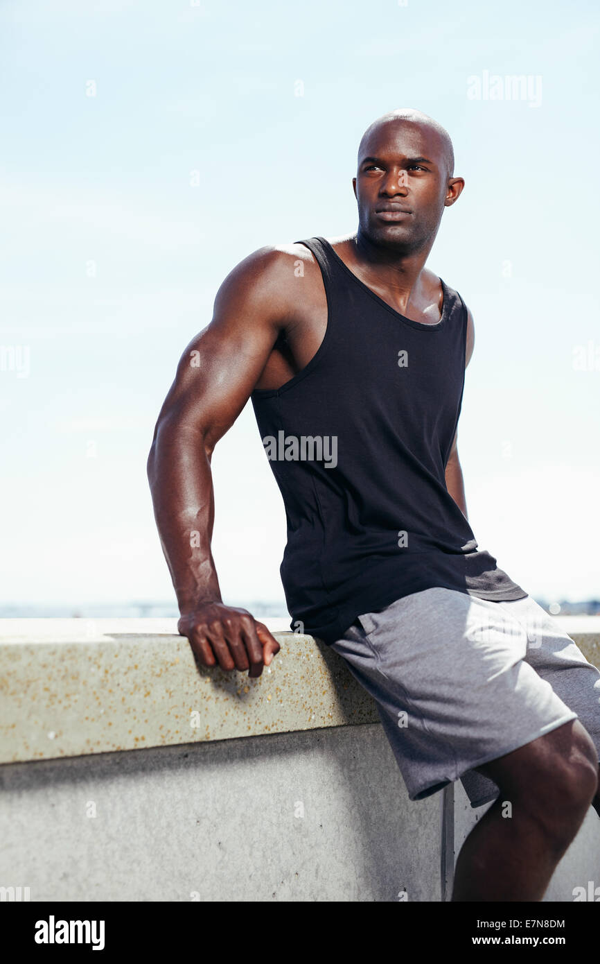 Outdoors shot of healthy young man sitting on a wall looking away seriously. Muscular African male model. - Stock Image